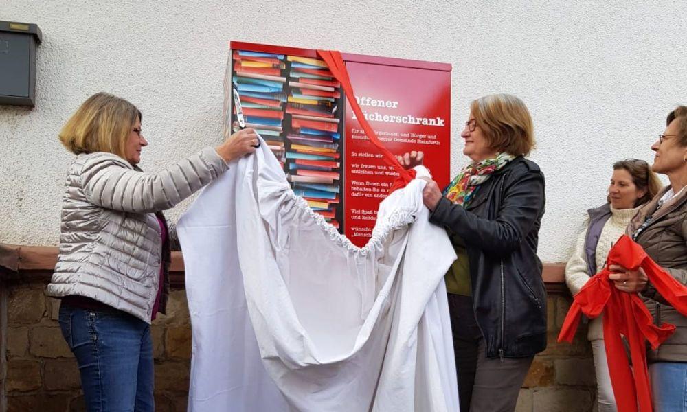 Auf dem Foto zum Bericht zur Eröffnung Bücherschrank sieht man Kathrin Schimmelpfennig (links) und Rosemarie Momberger (rechts) beim Enthüllen des Bücherschranks
